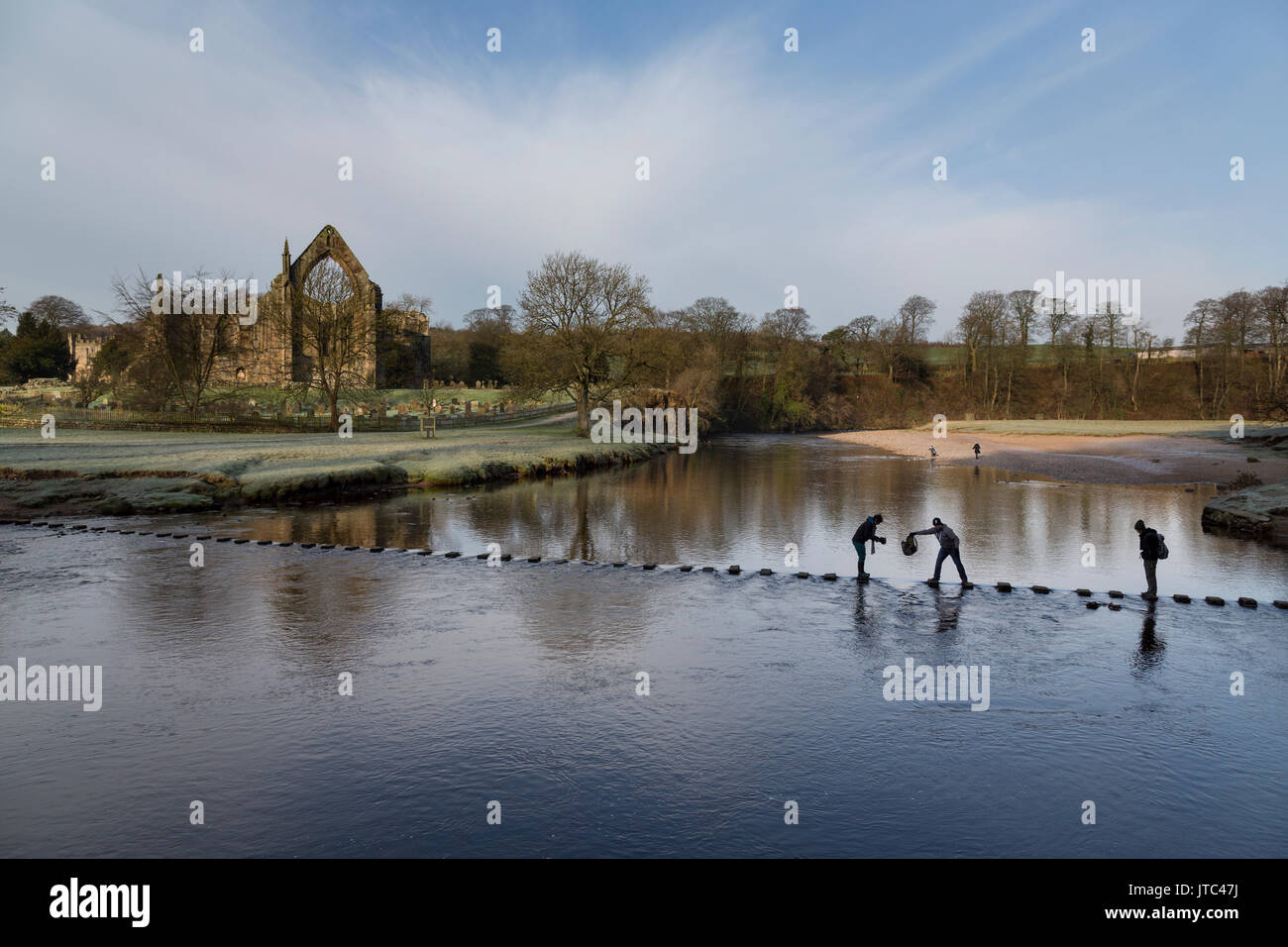 Bolton Abbey with people crossing the stepping stones over the river Wharfe in the Yorkshire Dales National Park - Stock Image
