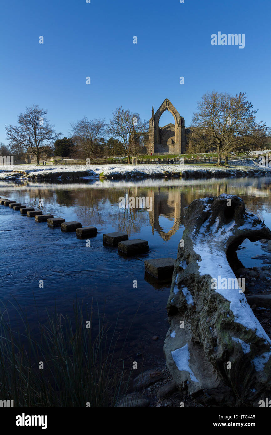 Bolton Abbey, North Yorkshire Dales National Park with stepping stones over the river Wharfe in winter with snow Stock Photo