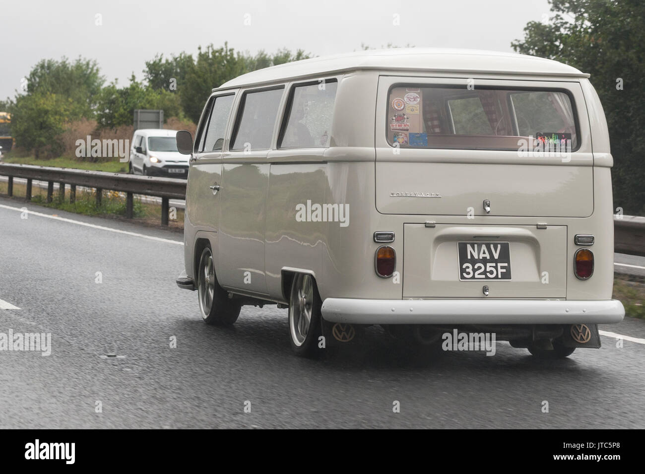 A classic VW campervan driving on a main road in the Uk - Stock Image