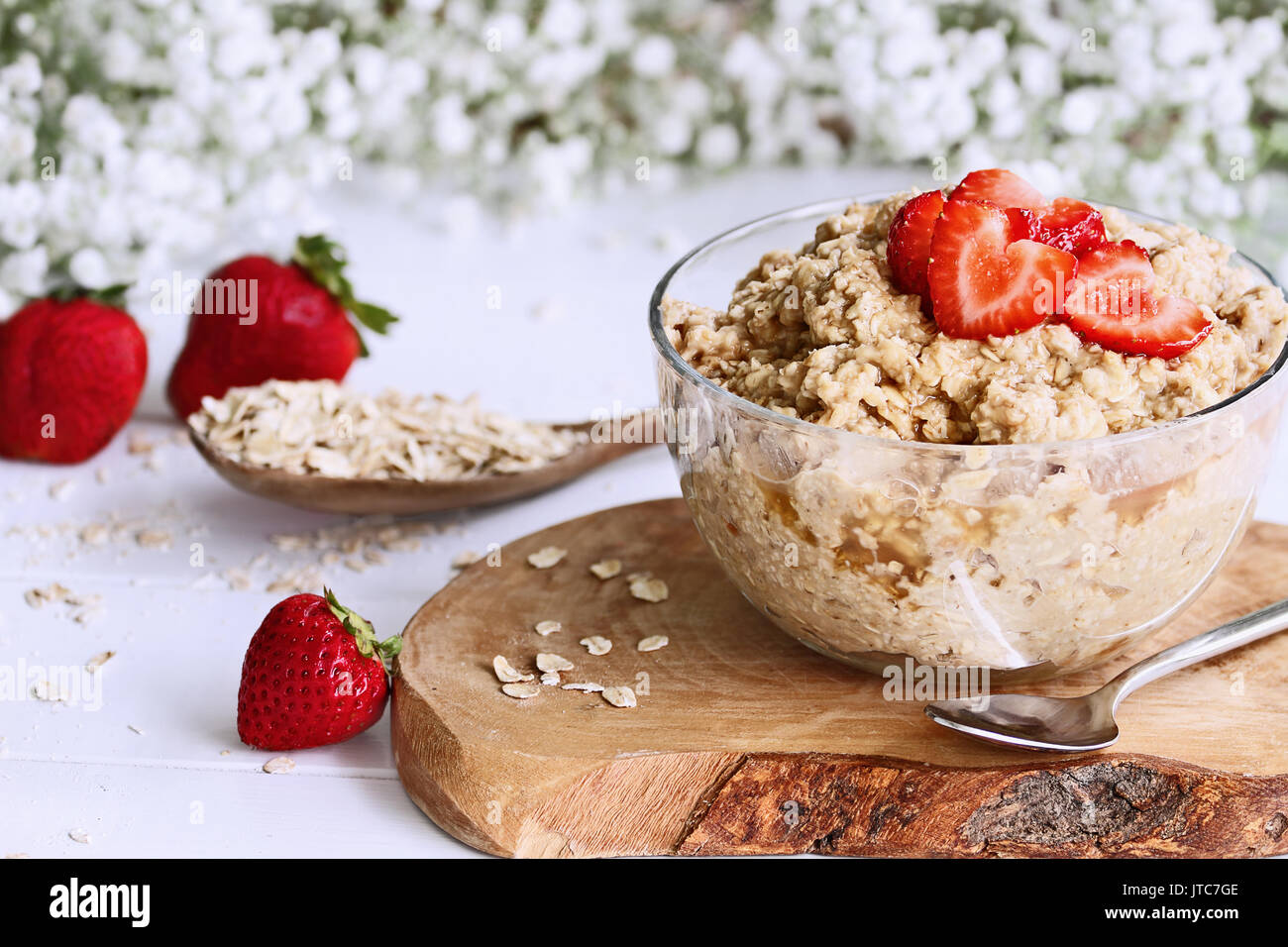Hot breakfast of healthy oatmeal and heart shaped strawberries. Selective focus with extreme shallow depth of field. - Stock Image