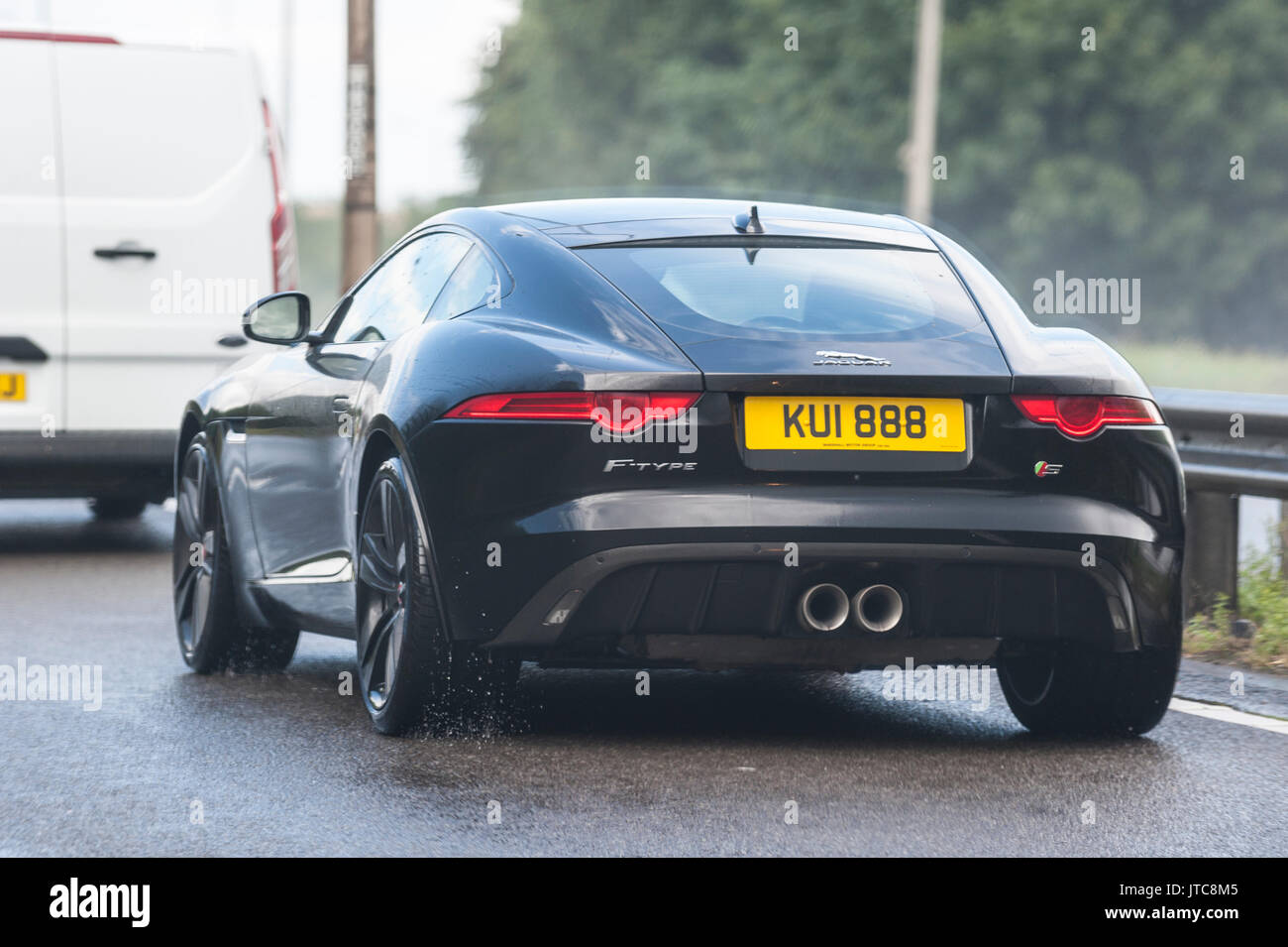 A Black Jaguar F Type Sports Car Driving In The Wet On A Main Road In Stock Photo Alamy