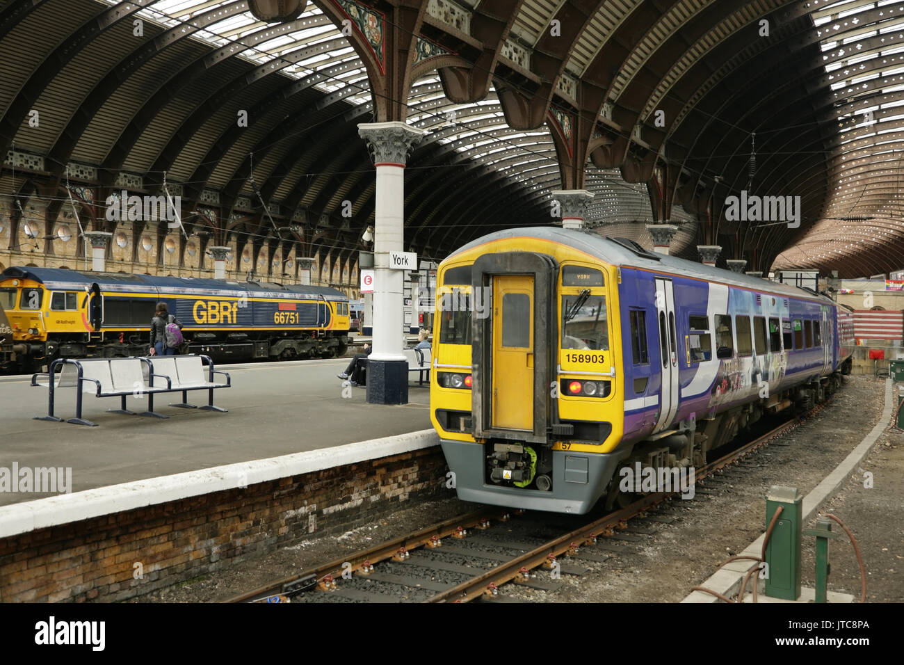 Northern rail class 158 diesel multiple unit standing at York station, UK while GBRF class 66 loco 66751 passes with northbound coal train. - Stock Image