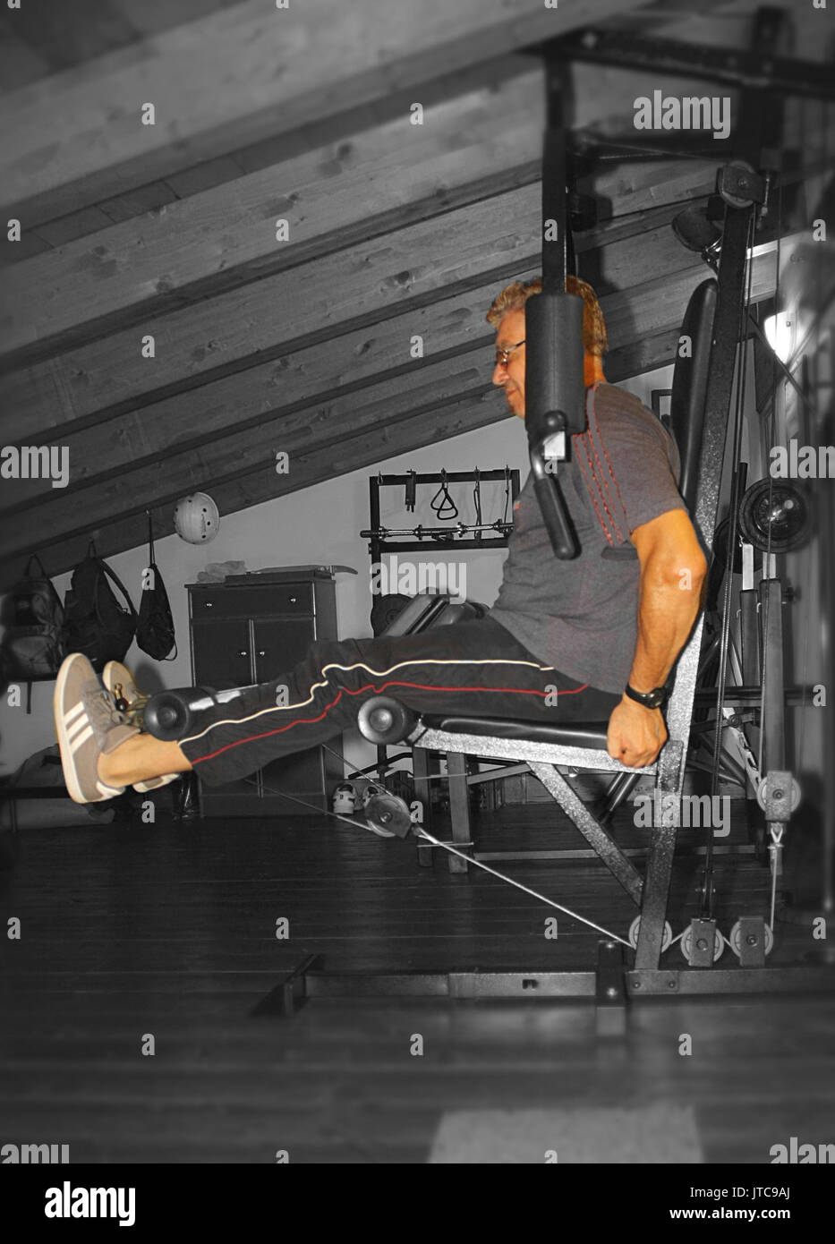 Home gym in the attic, Leg Extension - Stock Image