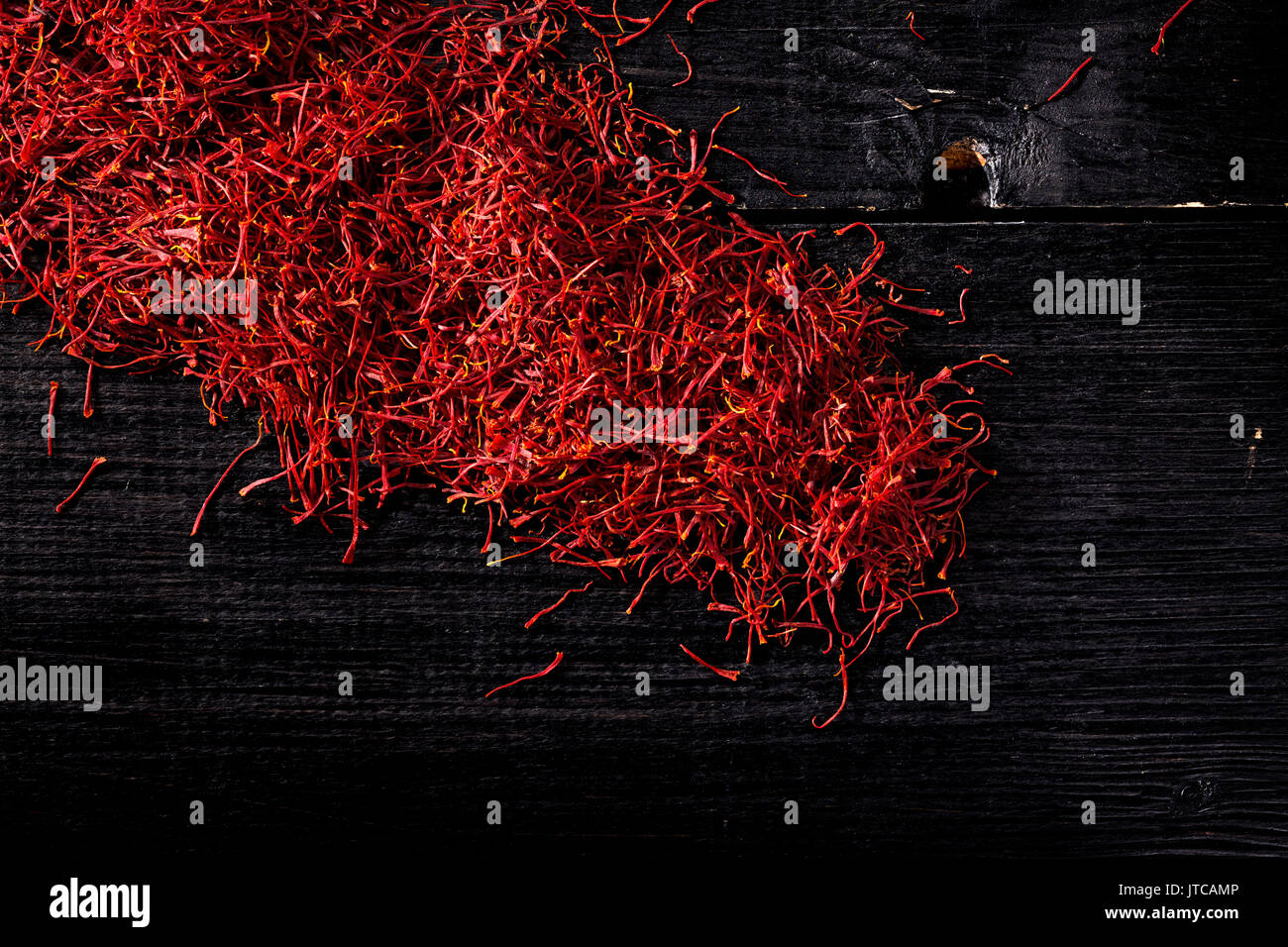 saffron crocus threads on black wooden board, view from above, backgrounds - Stock Image