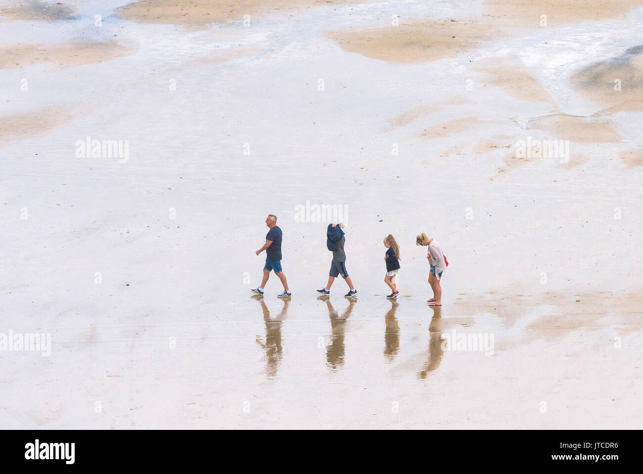 A family of holidaymakers walking in single file on a beach in Newquay, Cornwall. - Stock Image