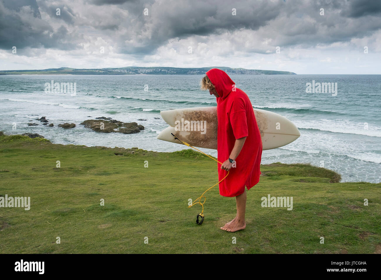 A surfer wearing a red surfing poncho holding a surfboard at Godrevy in Cornwall. - Stock Image