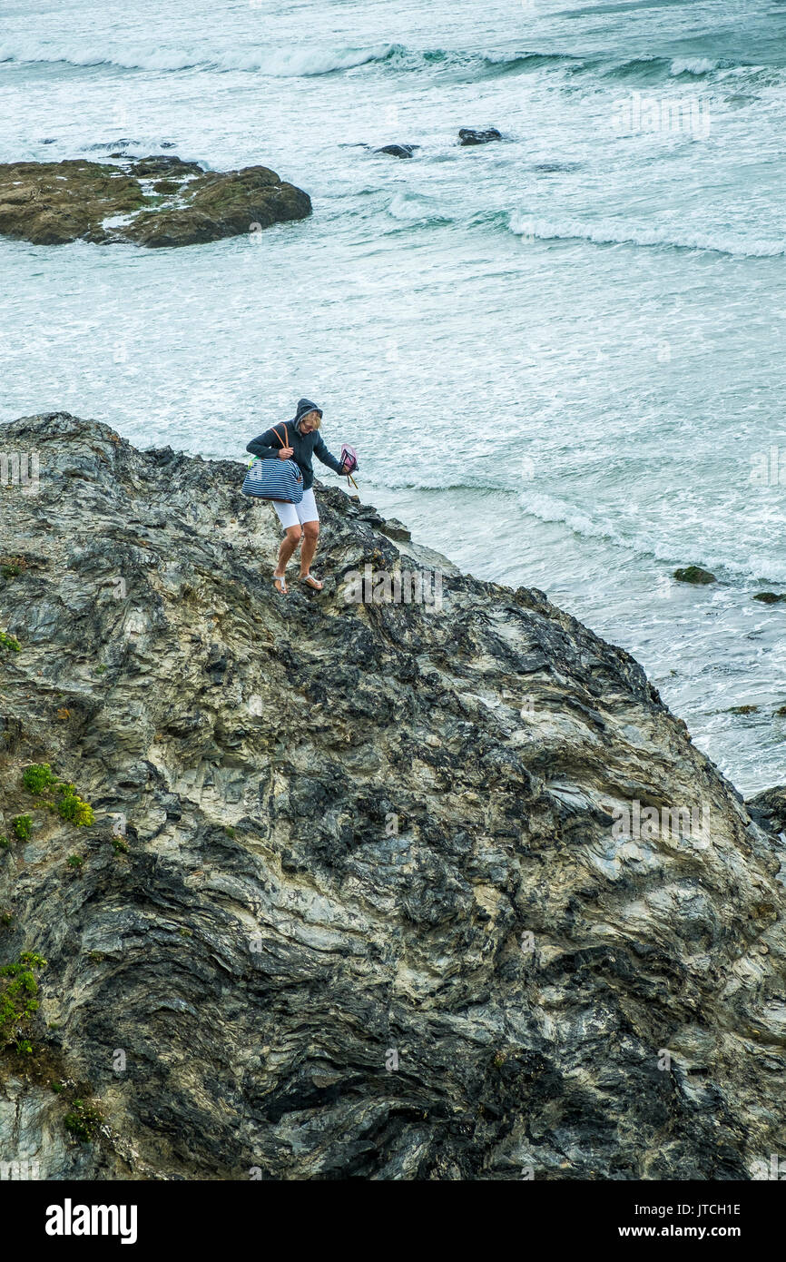 A woman climbing down slippery rocks at Godrevy Beach in Cornwall. - Stock Image