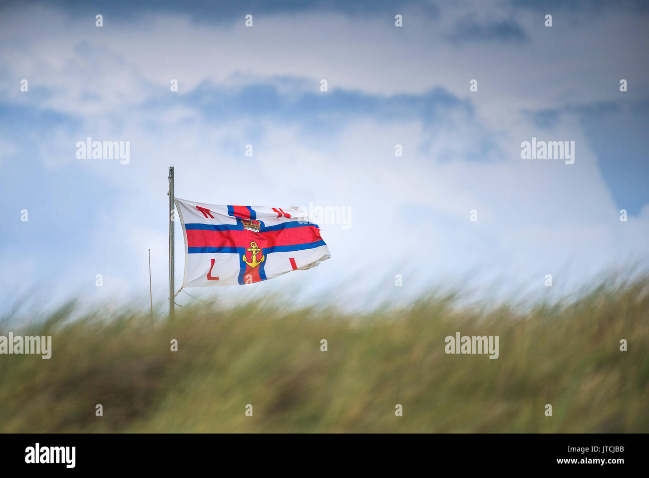 A RNLI flag fluttering in windy conditions. - Stock Image