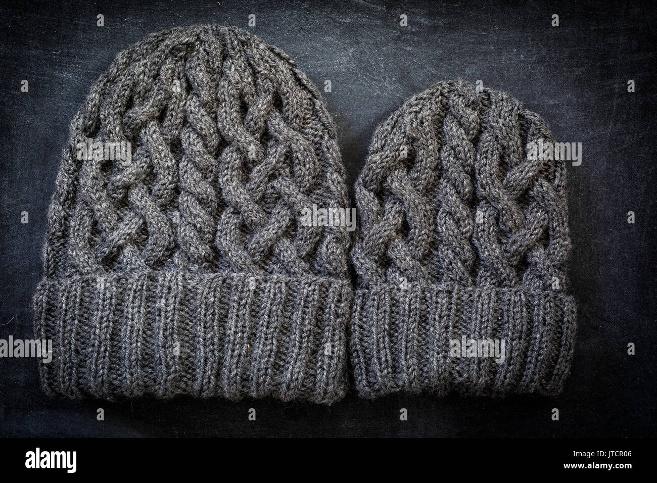 Two sizes of hand knit woolen hats with cables. One for a child, the other for an adult. - Stock Image