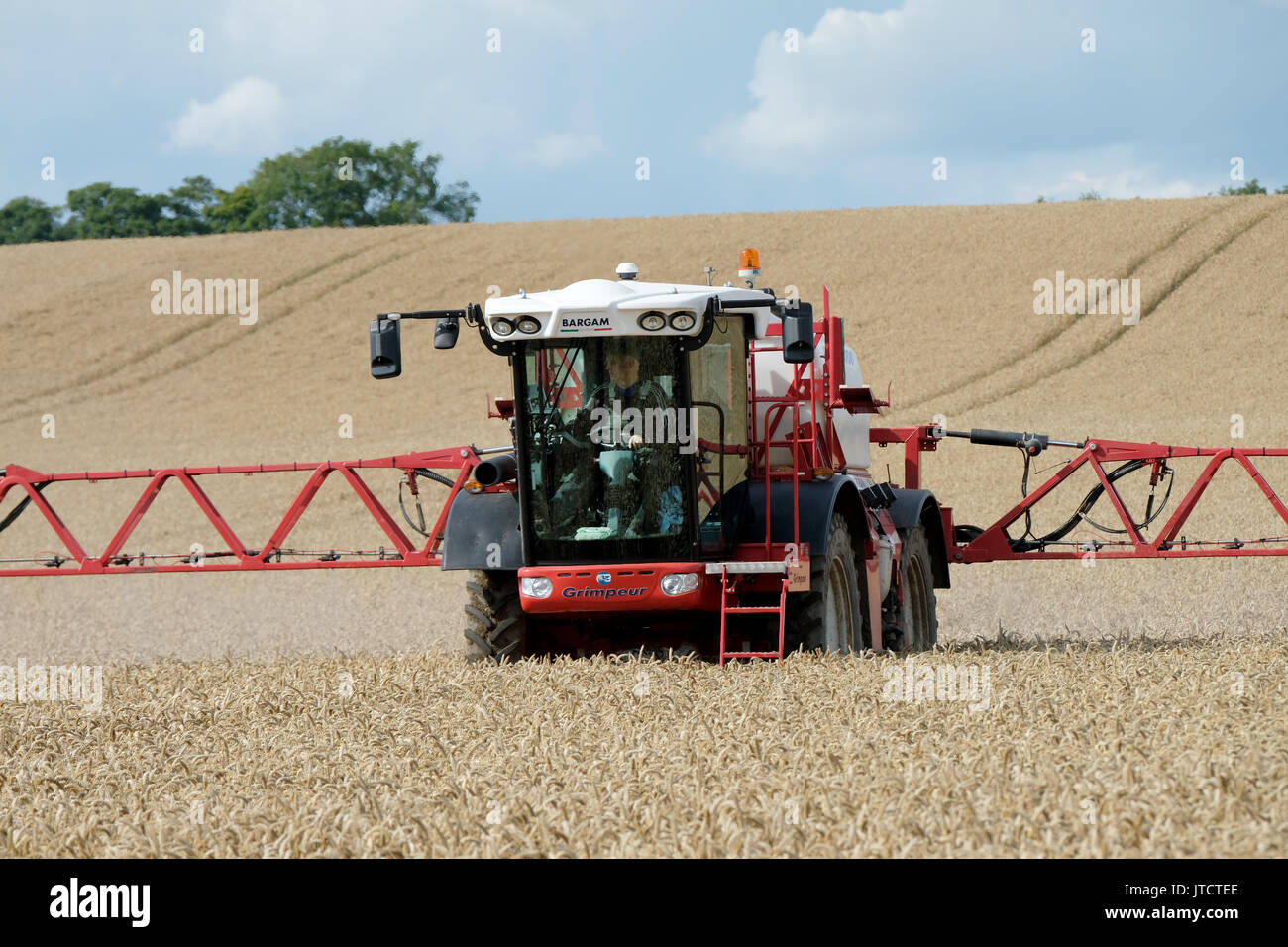 A crop spraying machine spraying a wheat field in West Lothian, Scotland. - Stock Image