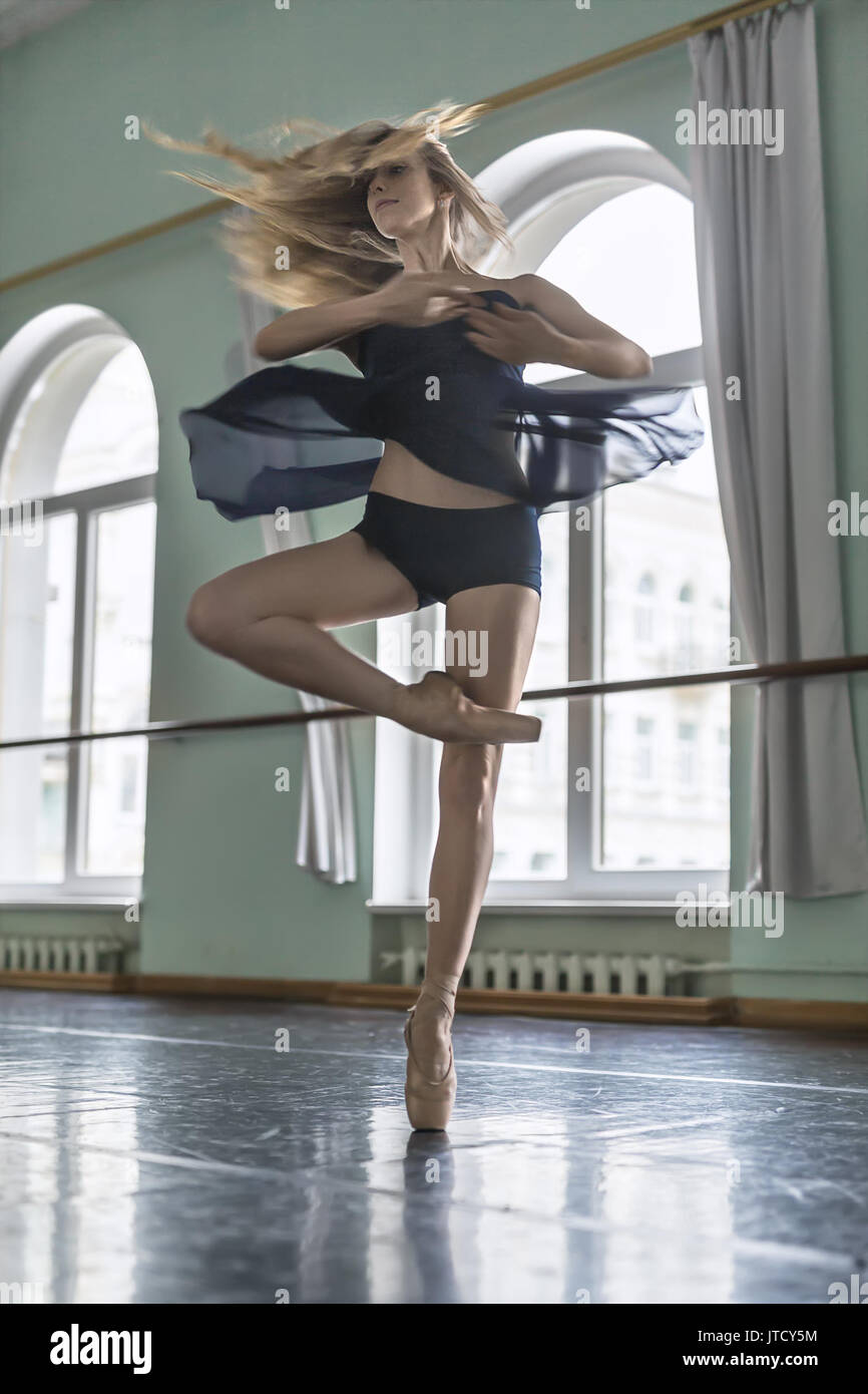 Young ballerina is posing in a motion in the ballet hall opposite large arch windows. She is circling on the left leg. Girl wears a dark dance wear an - Stock Image