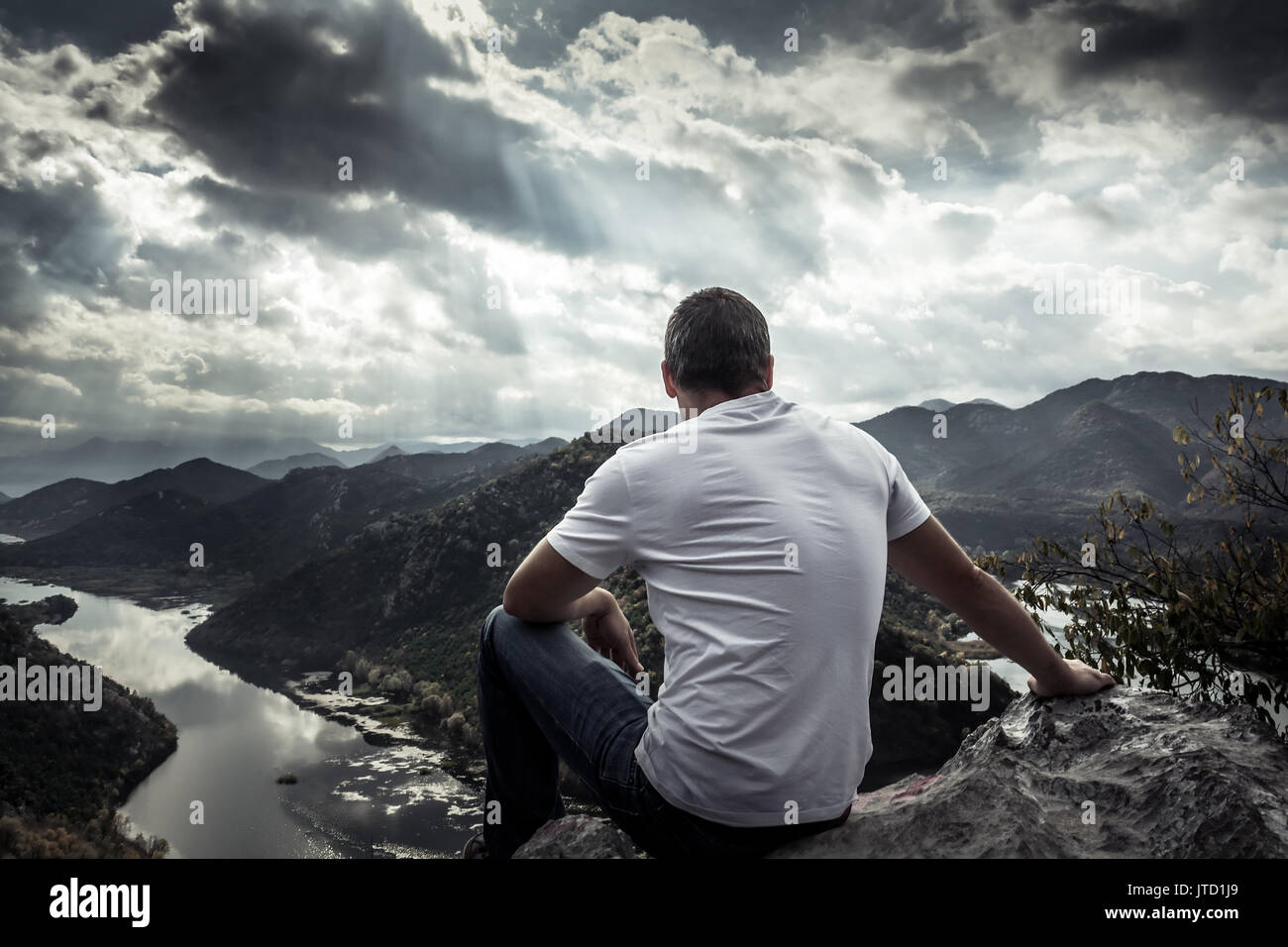 Lonely man looking with hope at horizon on mountain peak with dramatic sunlight during sunset with effect of light at the end of tunnel - Stock Image