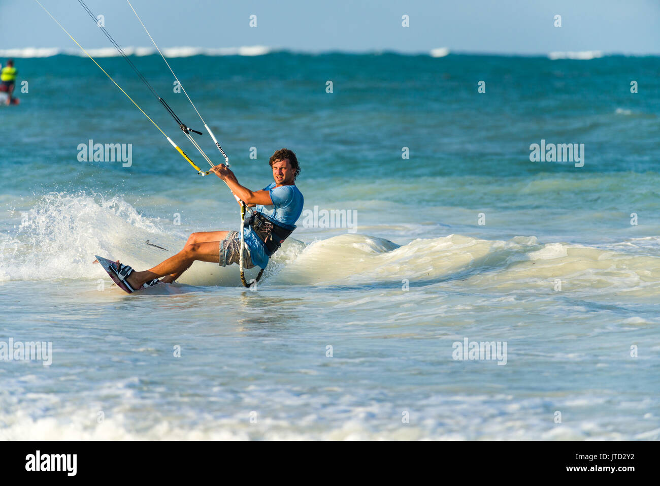 Kite surfer surfing close to shore on board in late afternoon light, Diani, Kenya - Stock Image