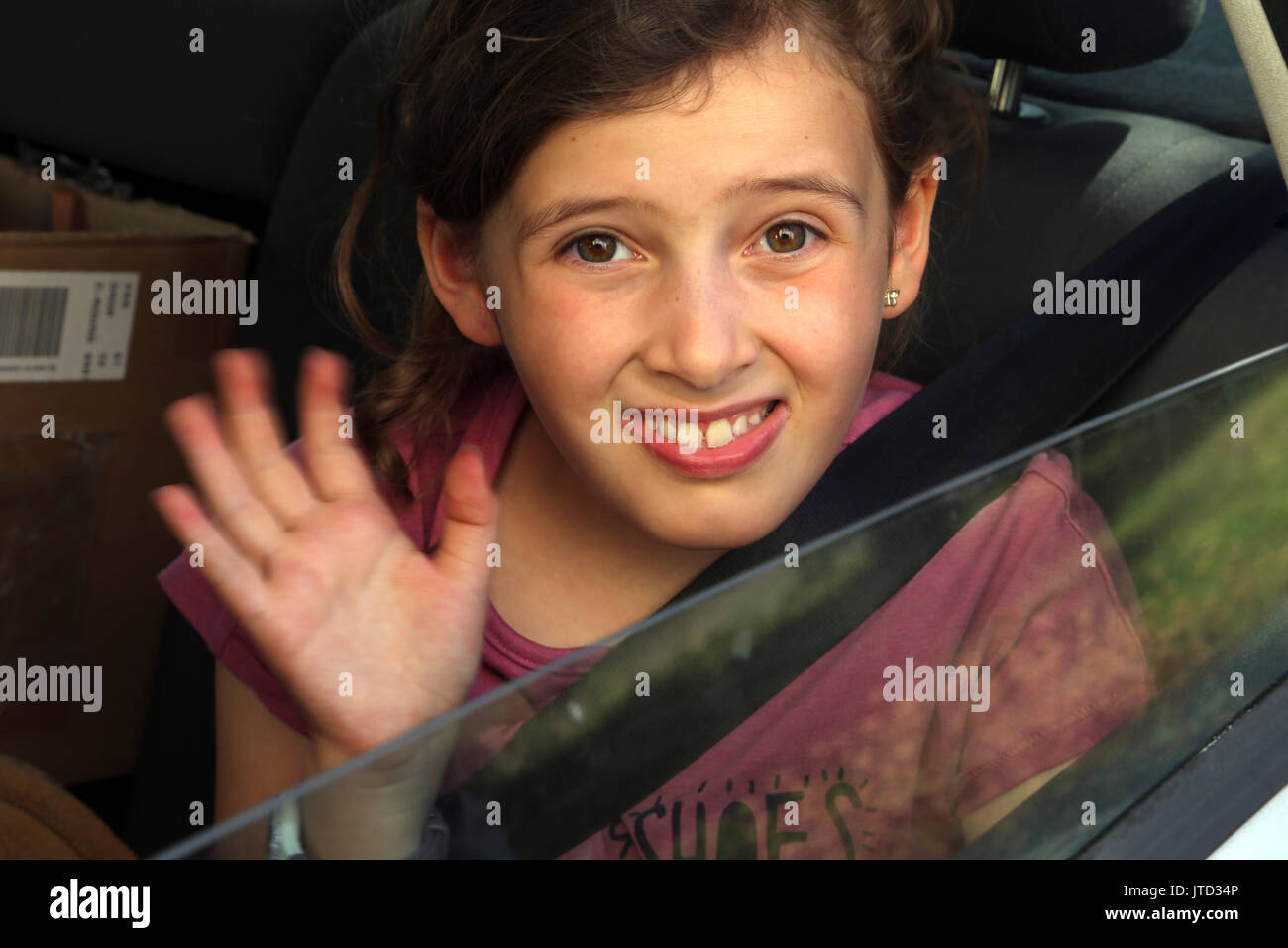 Young girl in car waving goodbye Surrey England - Stock Image