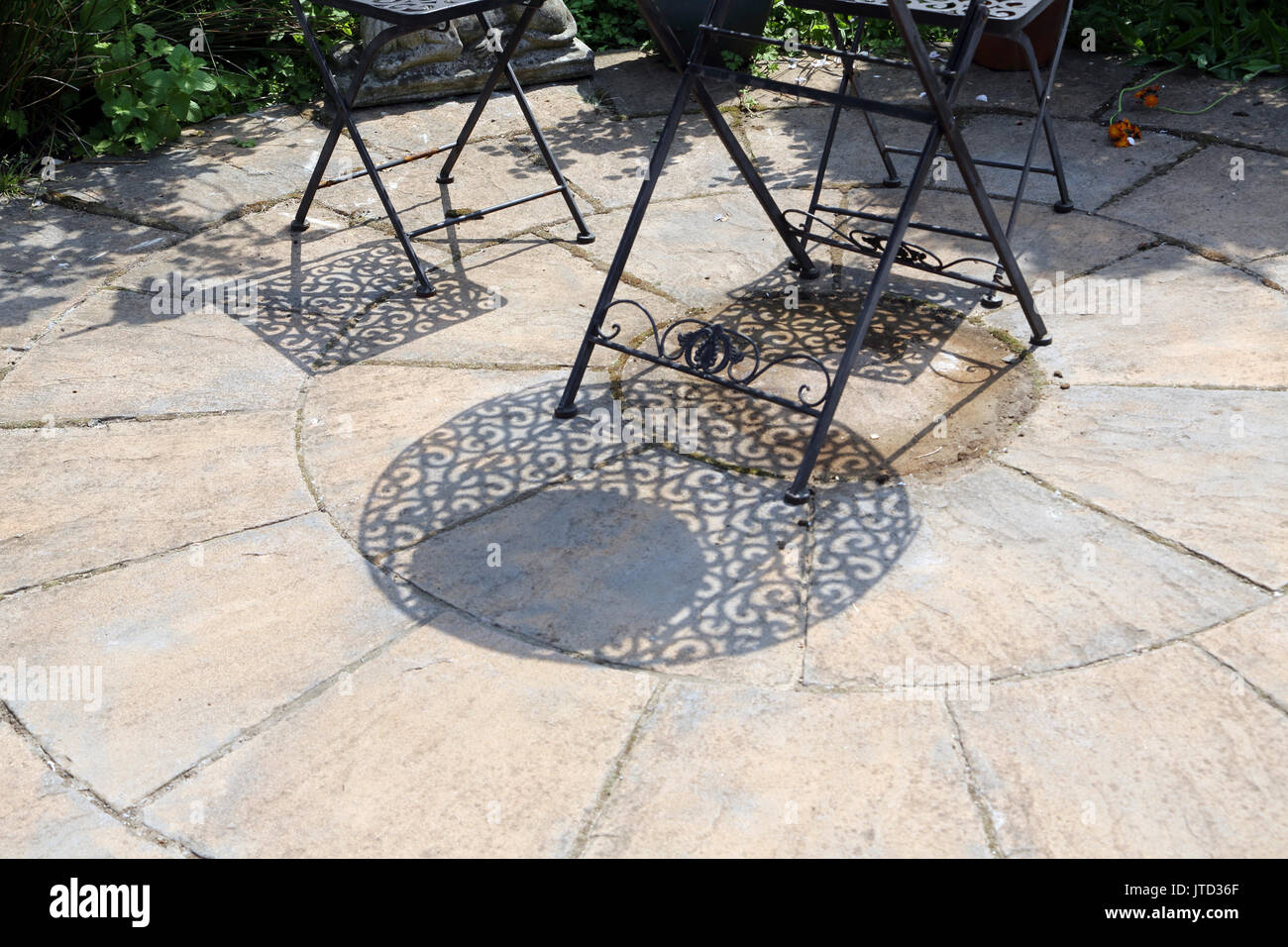 Wrought Iron Garden Furniture And Shadows In Summer Birmingham West  Midlands England   Stock Image