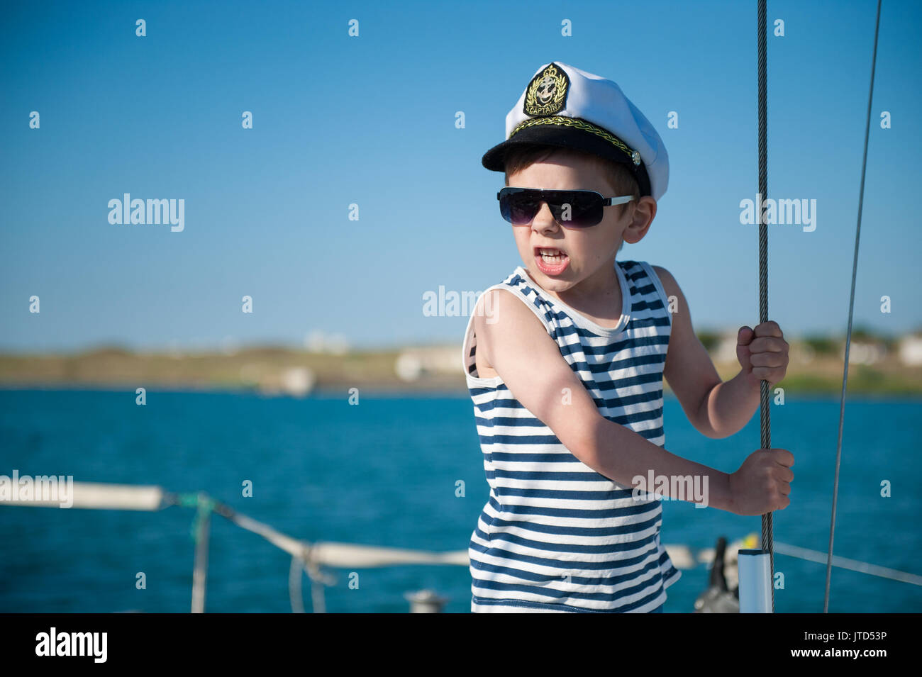 angry little boy captain shouting orders aboard vessel - Stock Image