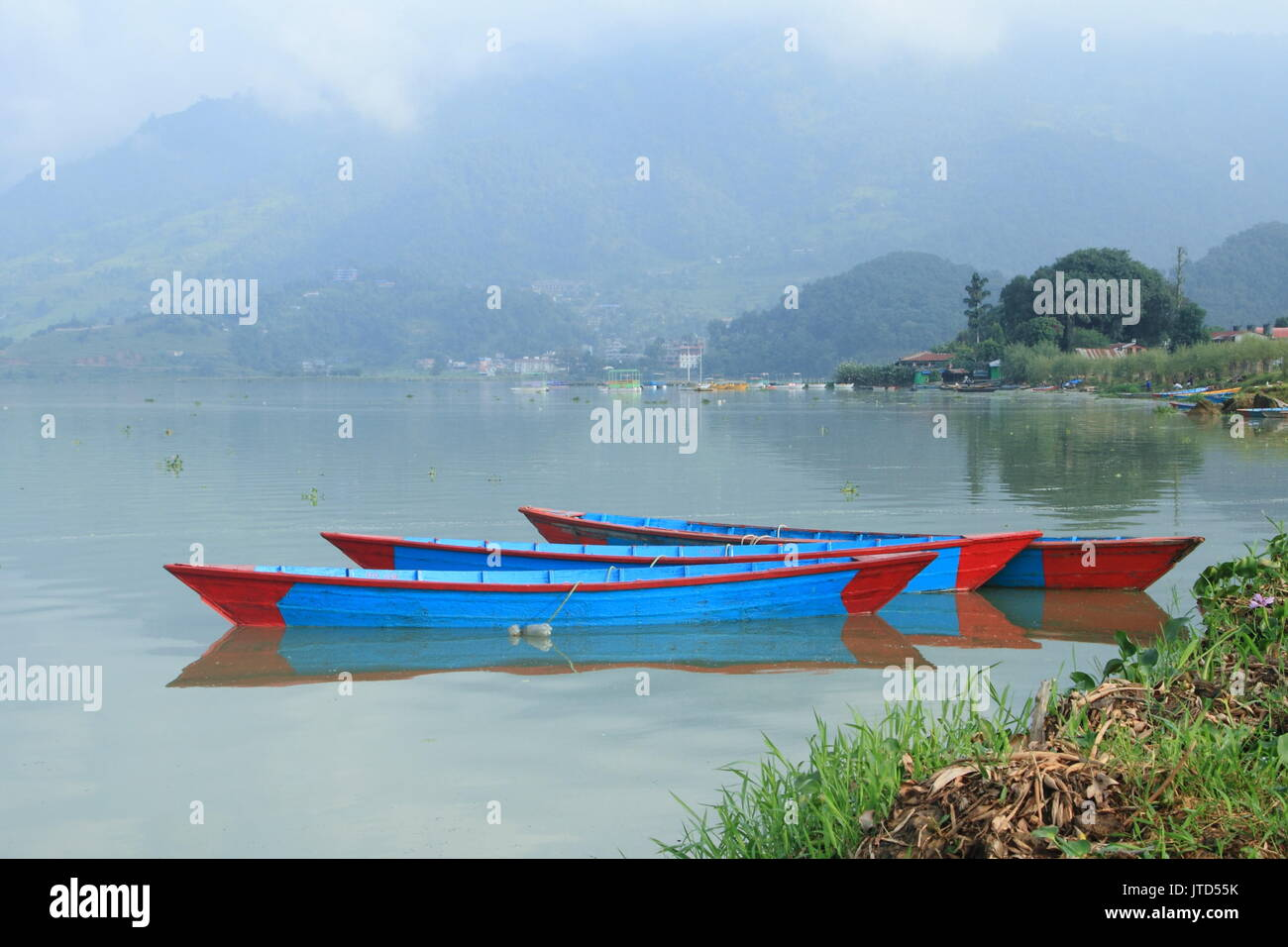 Pokhara / Nepal – September, 2015: colorful wooden boats at Phewa Lake, one of the Major tourist attractions of Nepal. - Stock Image