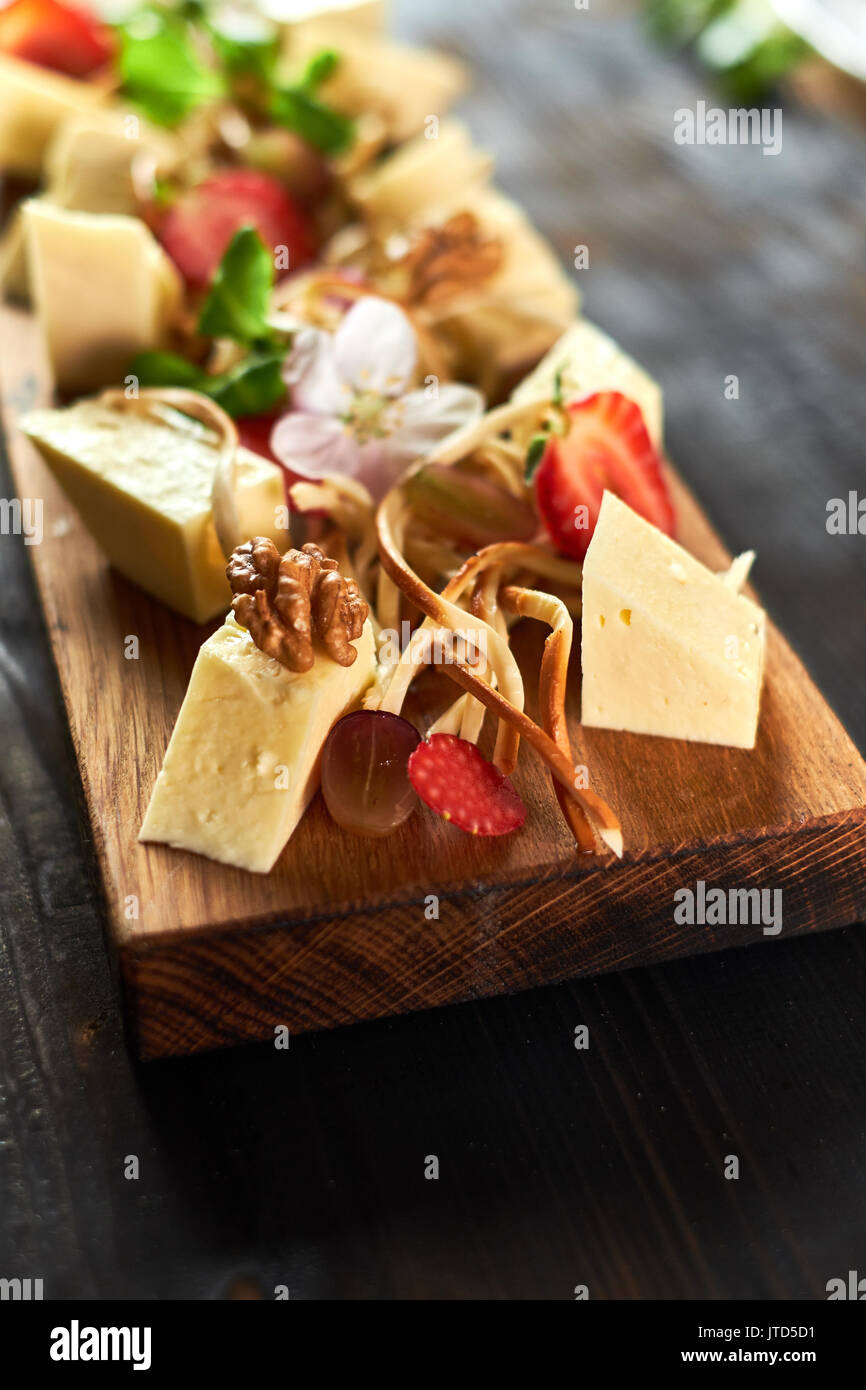Pieces of cheese on a board with vegetables hd Stock Photo