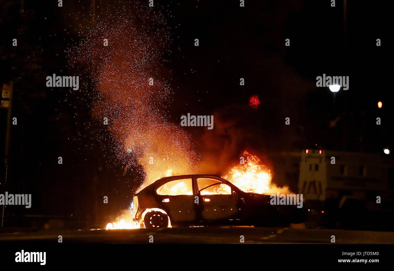 A car on fire in the North Queen Street area of Belfast, close to the site of a contentious bonfire. Stock Photo