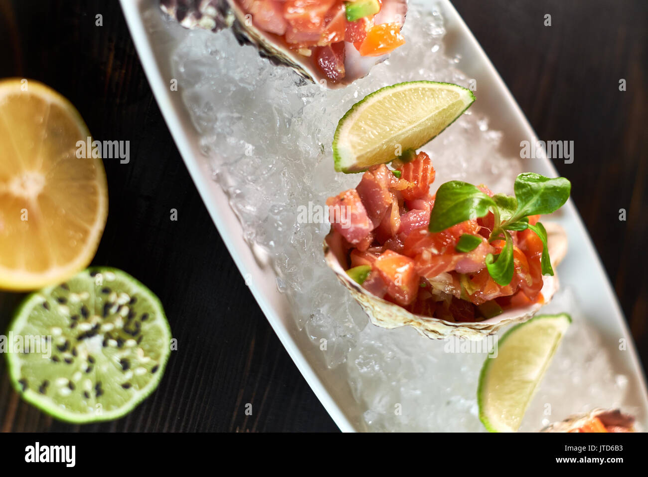 Delicious red fish in the shells of shellfish. With lemon and lime jpg - Stock Image
