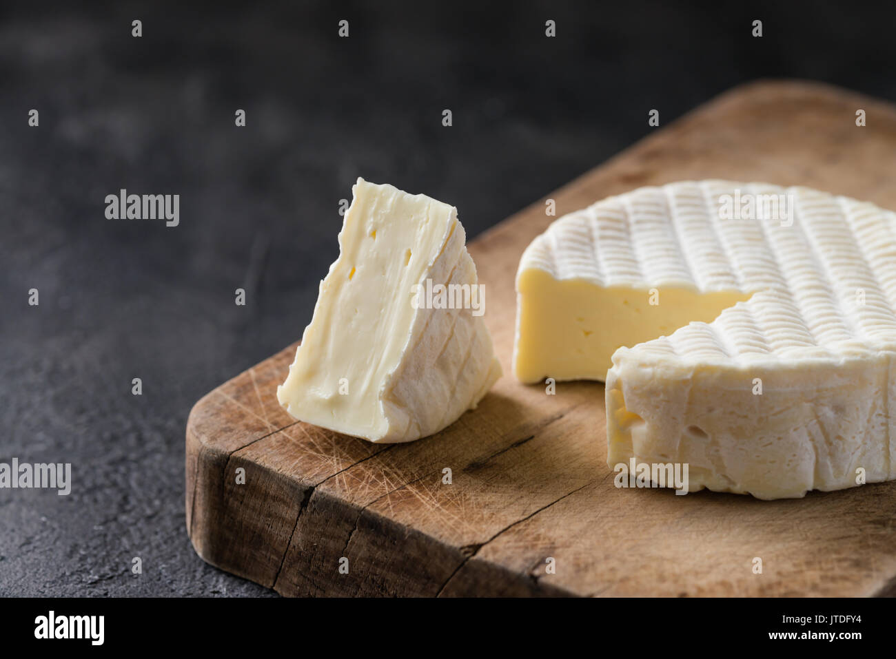 French soft cheese from Normandy region with a slice on a wooden board on dark rustic background - Stock Image