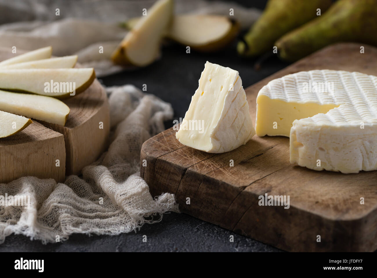 French soft cheese from Normandy region sliced with pear on a wooden board on dark rustic background - Stock Image