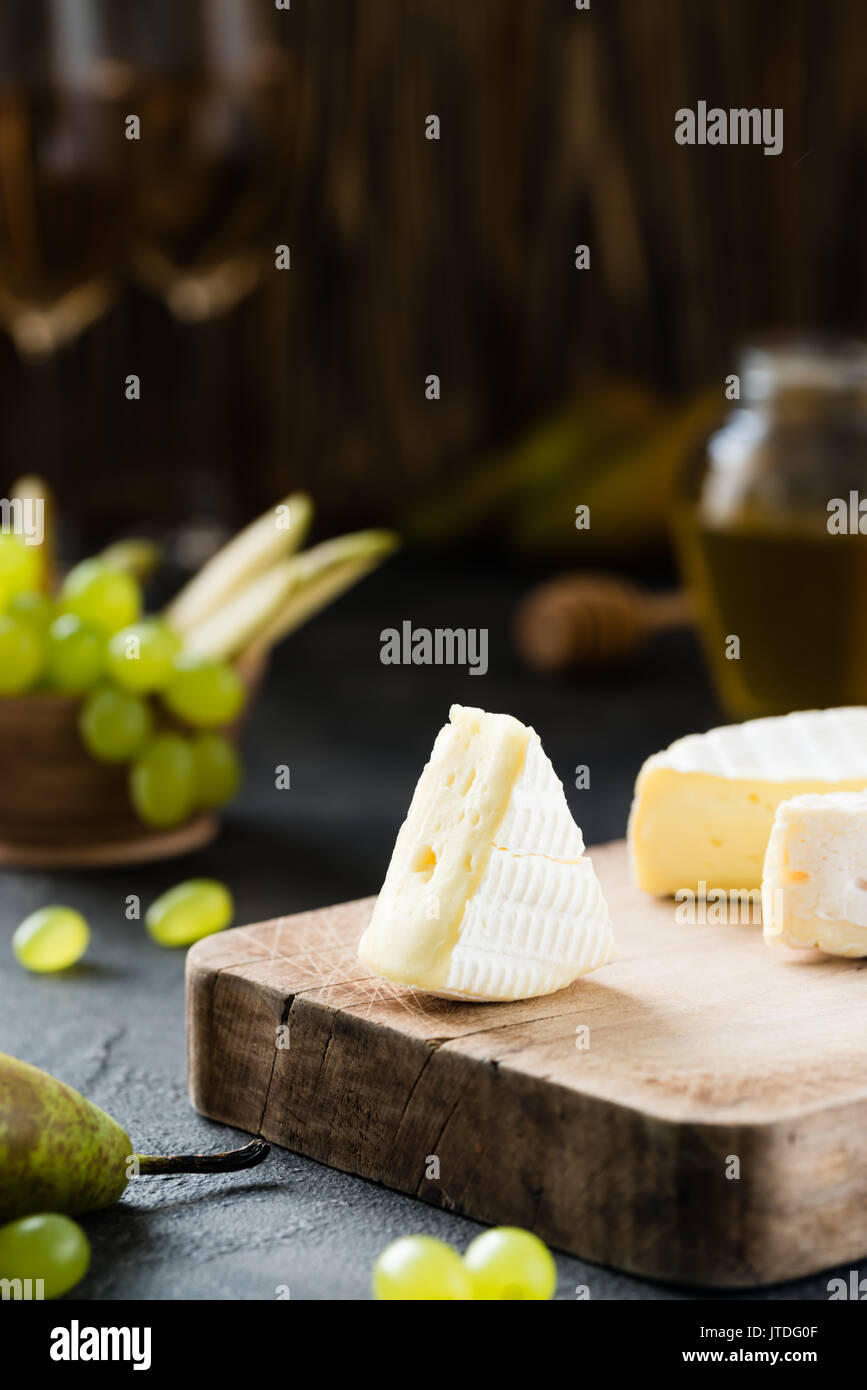 French soft cheese from Normandy region sliced with green grapes, pear, honey and glasses of wine on a wooden board on dark rustic background - Stock Image