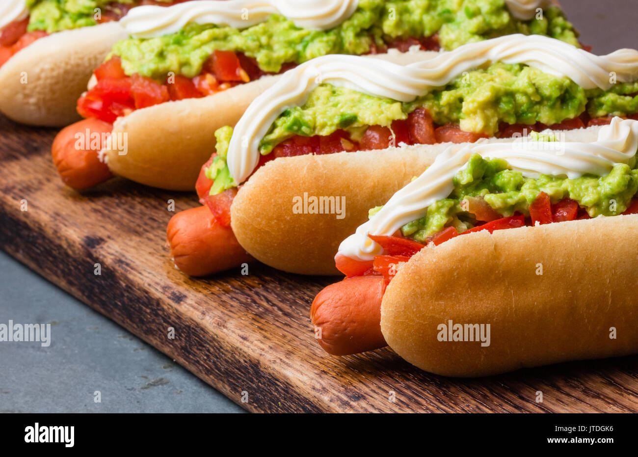 Chilean Completo Italiano. Hot dog sandwiches with tomato, avocado and mayonnaise on wooden board. closeup. - Stock Image
