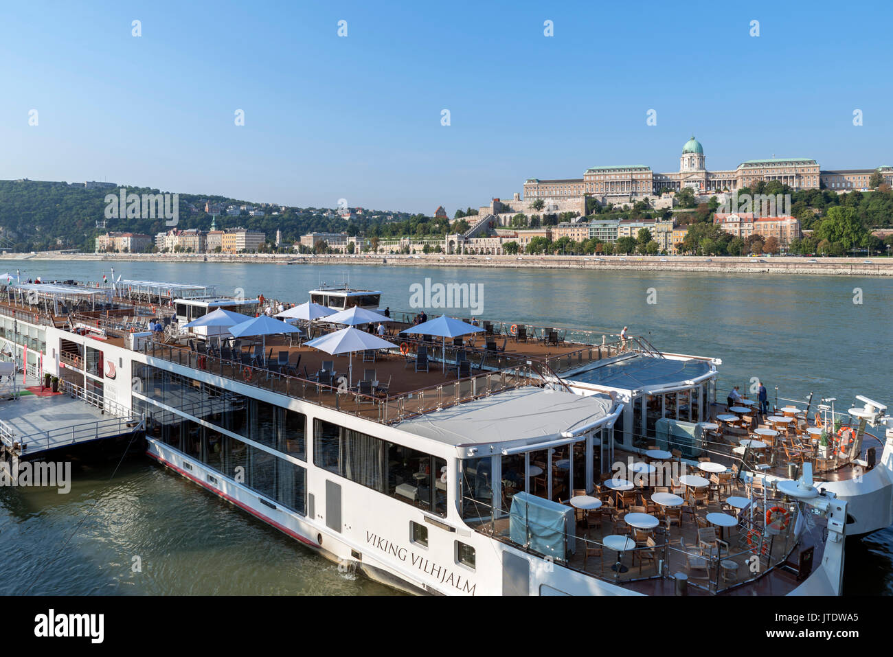 Viking River Cruises cruise boats with The Royal Palace on Castle Hill behind, Budapest, Hungary - Stock Image