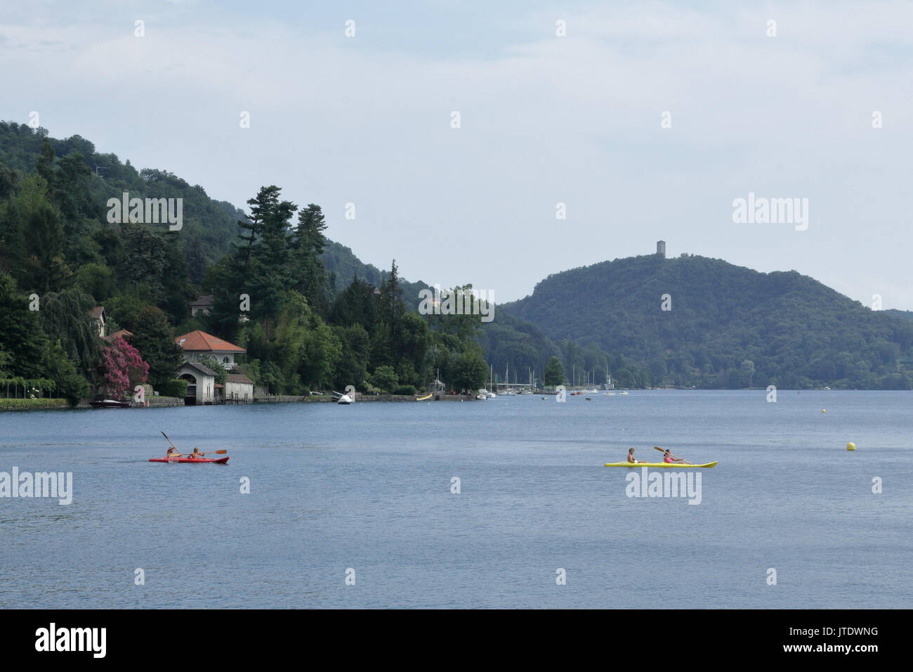 A house with trees next to the lake Orta shore in Novara province, northern Italy, with two pirogues - Stock Image