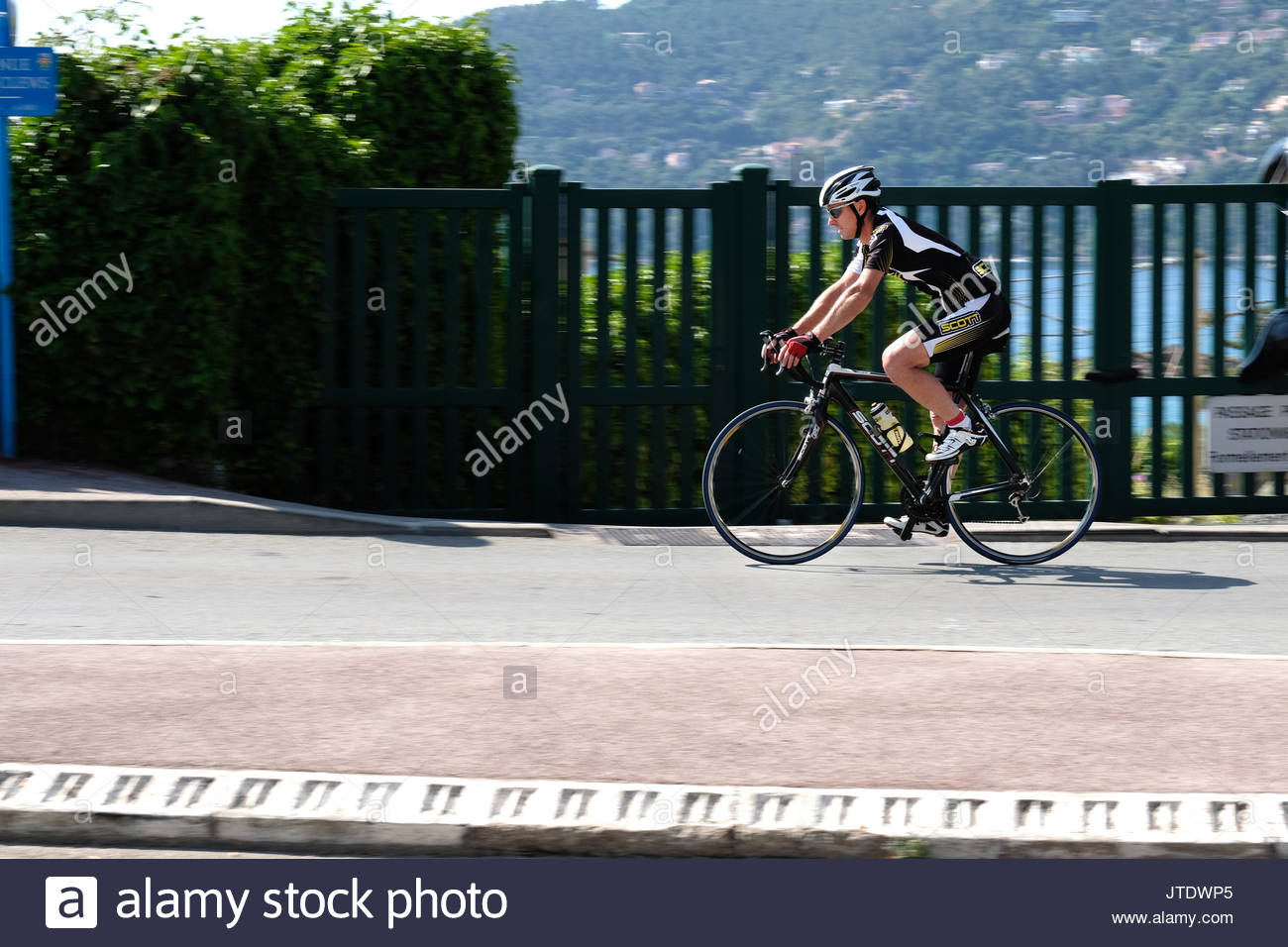 A middle aged male cycling enthusiast,in exam colours,riding his bike, at speed, along a coast road in the south of France - Stock Image
