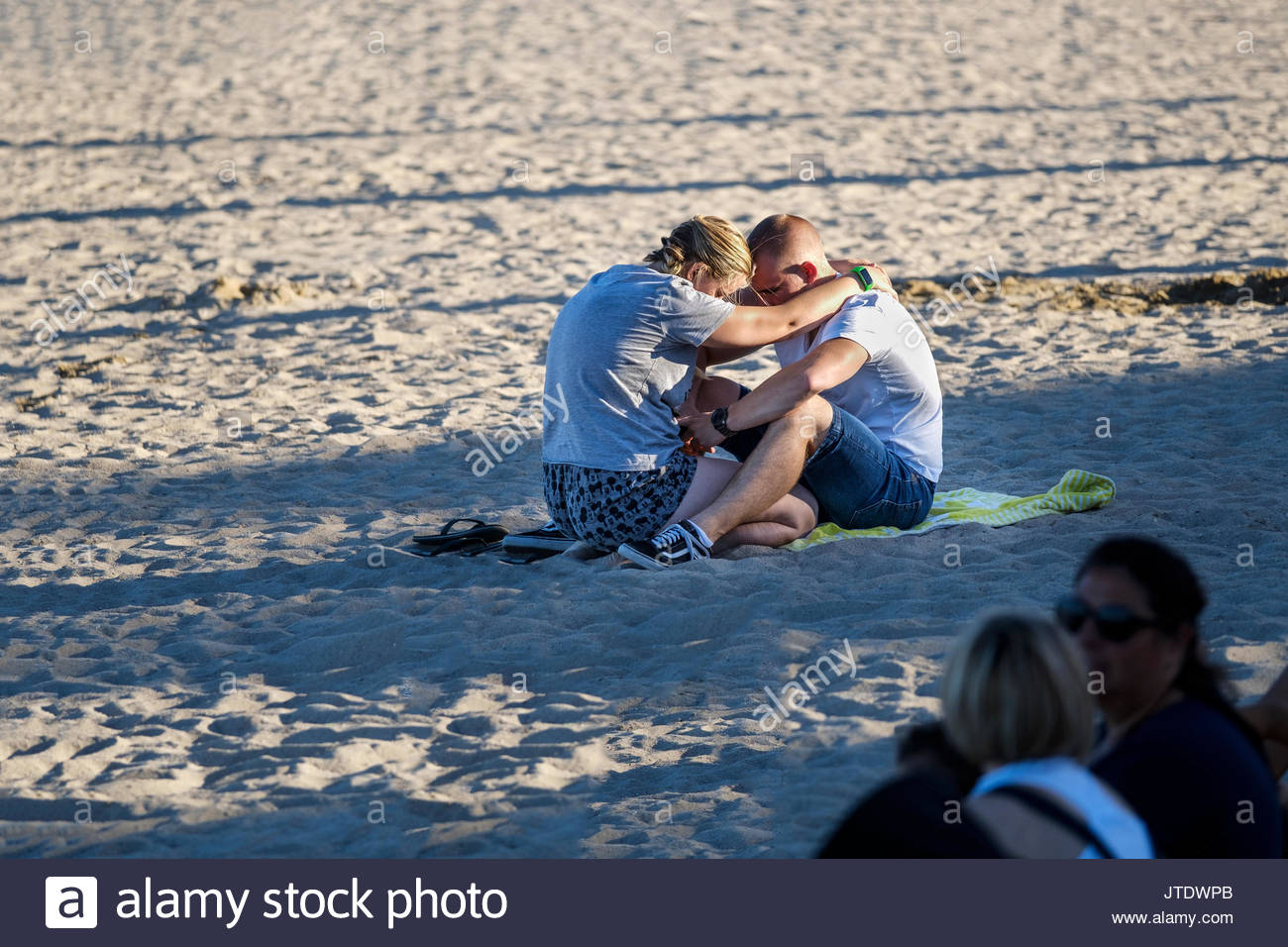 A woman consoling and offering sympathy o an upset emotional man and cuddled together on a beach - Stock Image