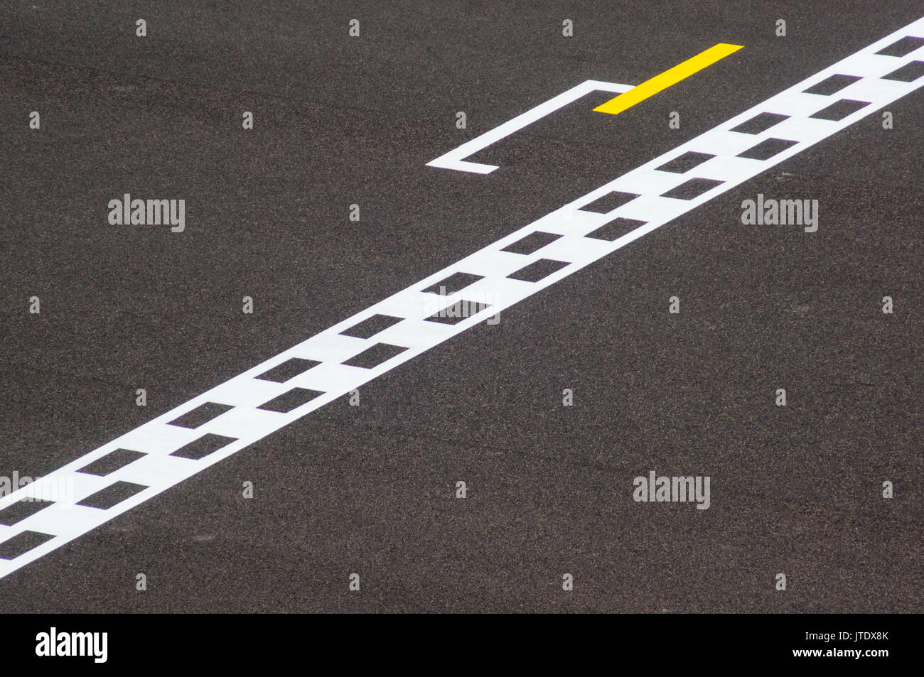 Minimalistic photo of a chequered finish line on a track. Signifies the end of a project or event - Stock Image