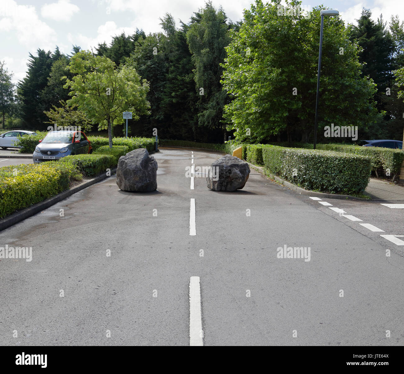 A small roadway that has been blocked with two huge lumps of rock positioned in the middle of each lane preventing enything other than a bike past it. - Stock Image
