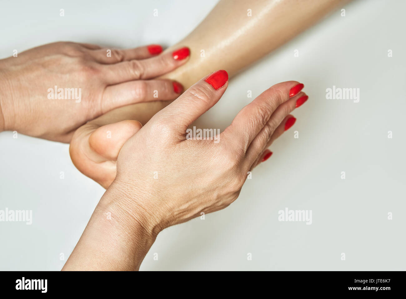 Hands of professional masseuse applying pressure on toes to release the foot stress. Spa and Wellness. Closeup. - Stock Image