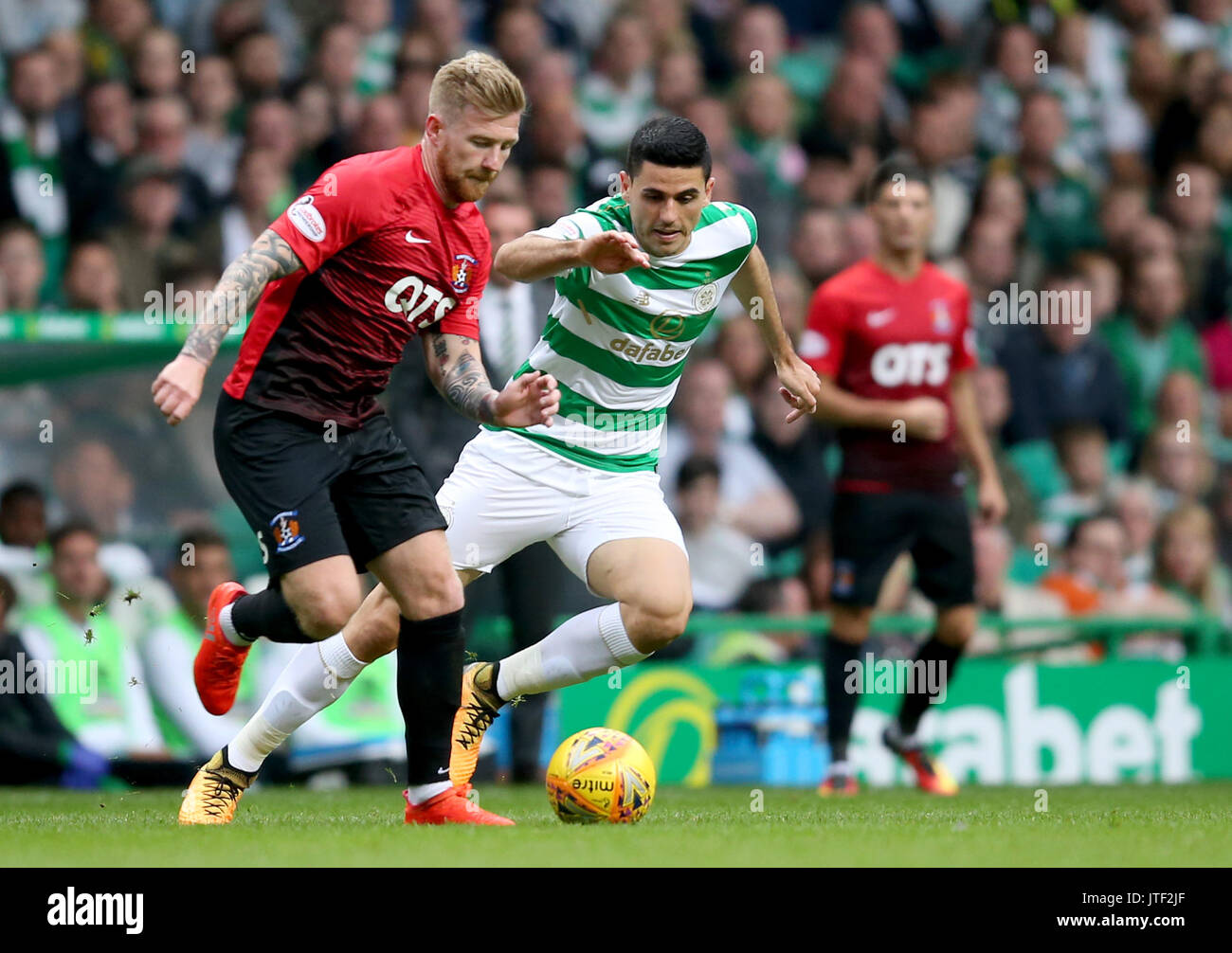Celtic's Tom Rogic and Kilmarnock's Alan Power battle for the ball during the Betfred Cup, Second Round match at Celtic Park, Glasgow. - Stock Image