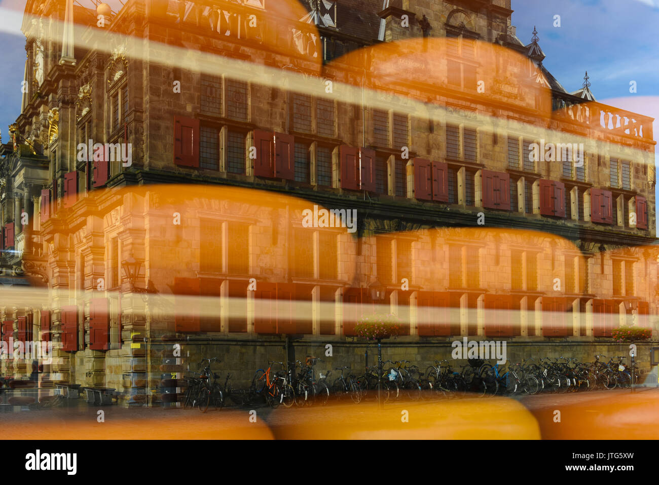 The Stadhuis or City Hall reflected in the window of a cheese shop in Delft, South Holland, The Netherlands - Stock Image