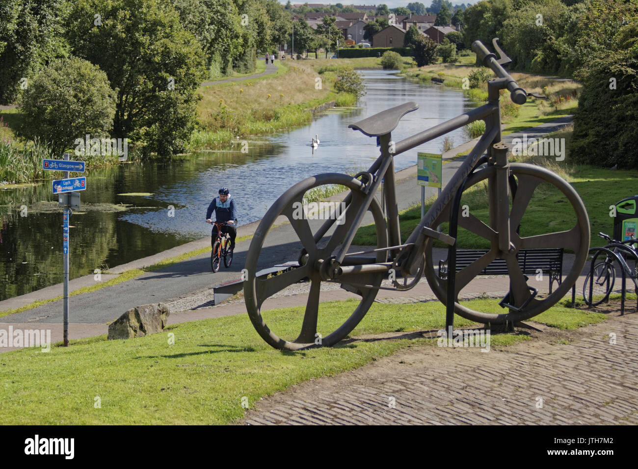 Clydebank, Glasgow, Scotland, UK. 9th August .Cyclists on NCN 7 pass the Bankies bike sculpture at Clydebank  Summer weather returns and locals enjoy the summer  on the Forth and Clyde canal as Scotland catches the sun and the UK suffers different  weather Credit: gerard ferry/Alamy Live News - Stock Image