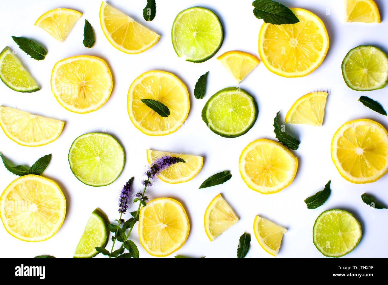 Lemon and lime slices with mint leaves on white background - Stock Image
