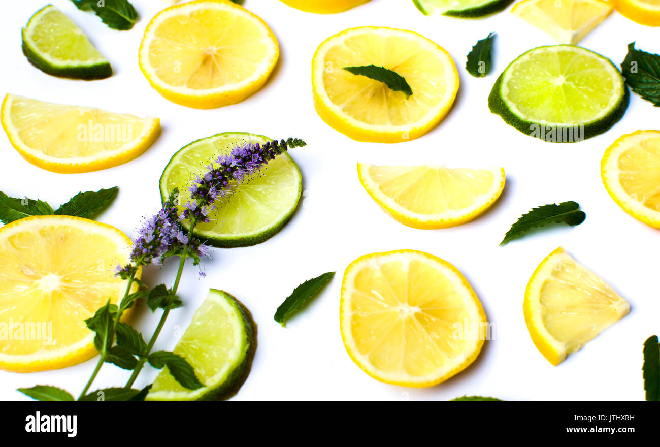 Lemon and lime slices with mint leaves on white - Stock Image