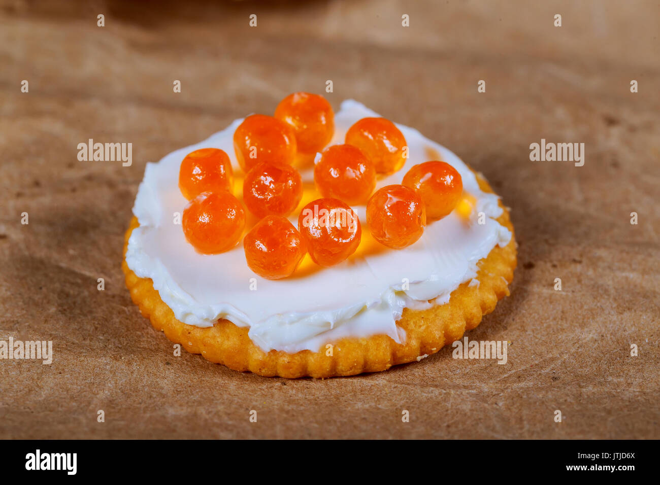 Caviar on the cracker red caviar on plate. Caviar on the background of a wooden table - Stock Image
