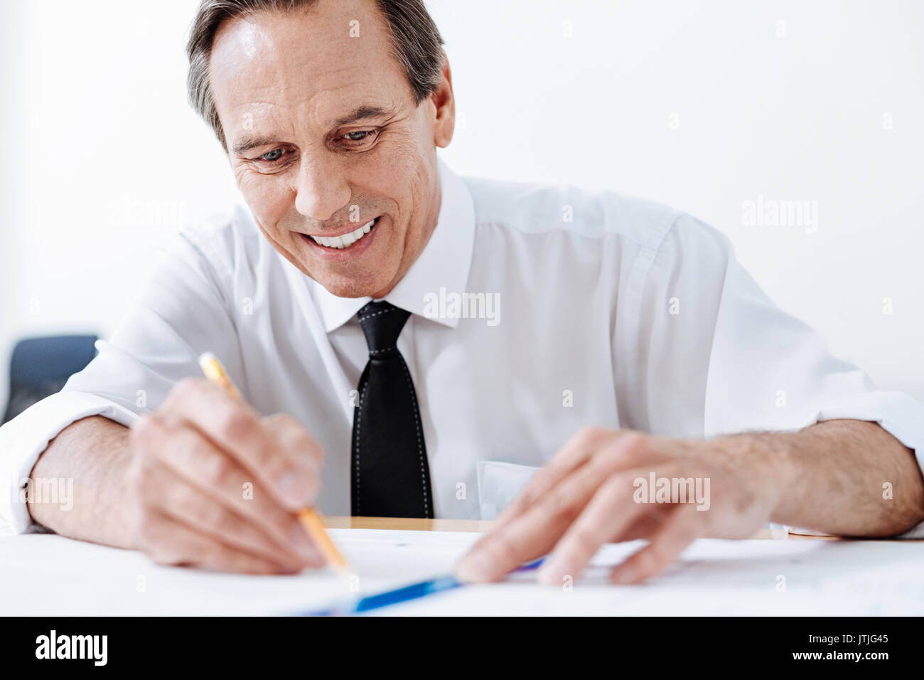 Pleasant man tracing lines on a blueprint - Stock Image