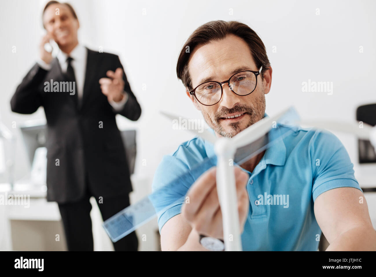 Engineer measuring wind turbine sail length with ruler - Stock Image