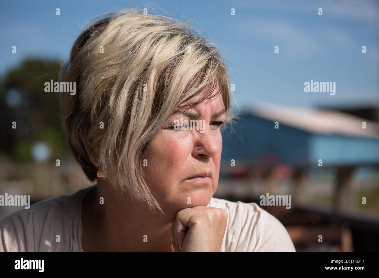 Contemplative mature Caucasian Swedish woman squinting into the sun. - Stock Image
