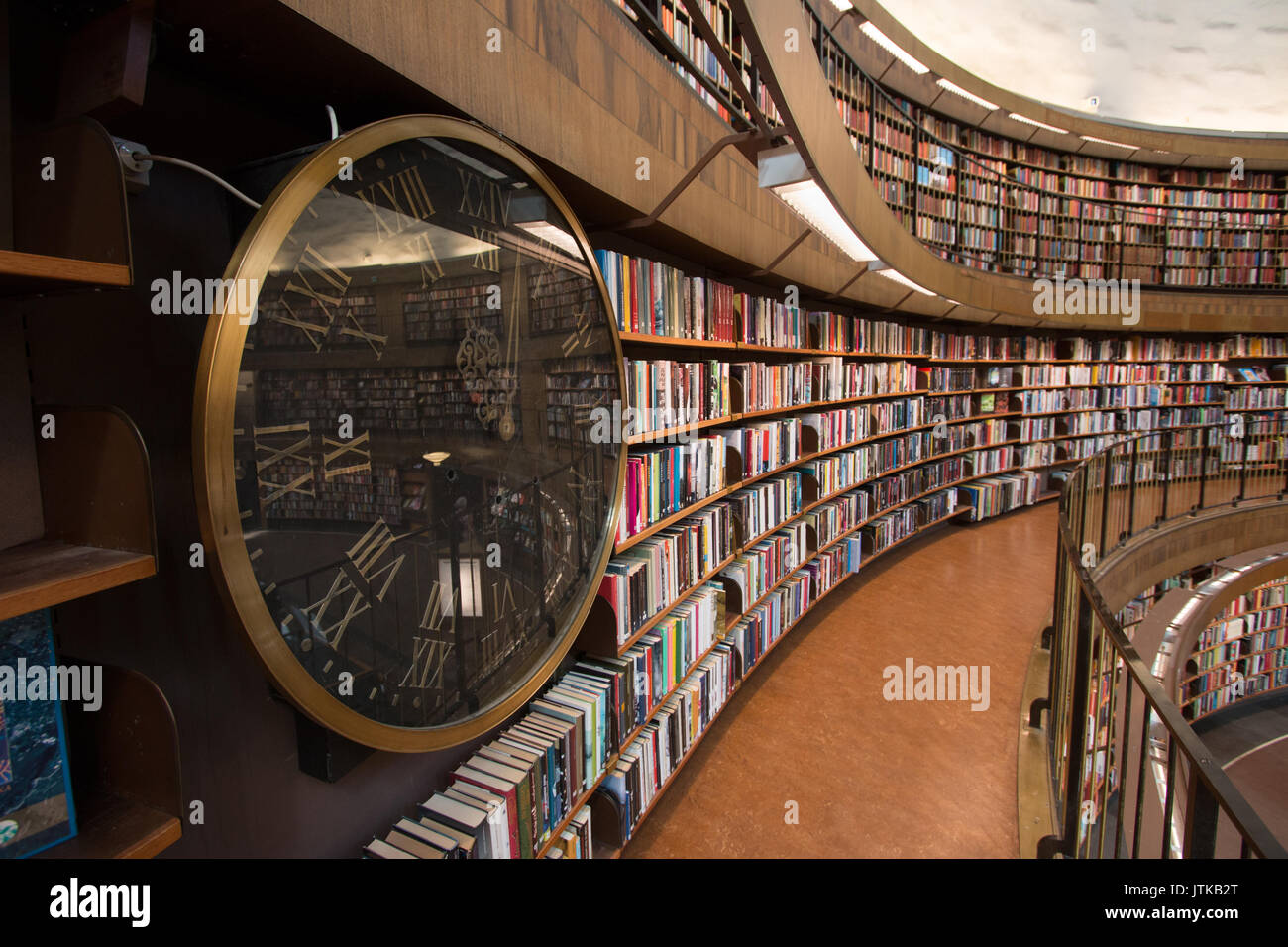 Knowledge is timeless. A wall clock at the beginning of a bookshelf, interior in Stockholm's municipal library, designed by Gunnar Asplund in 1928. - Stock Image
