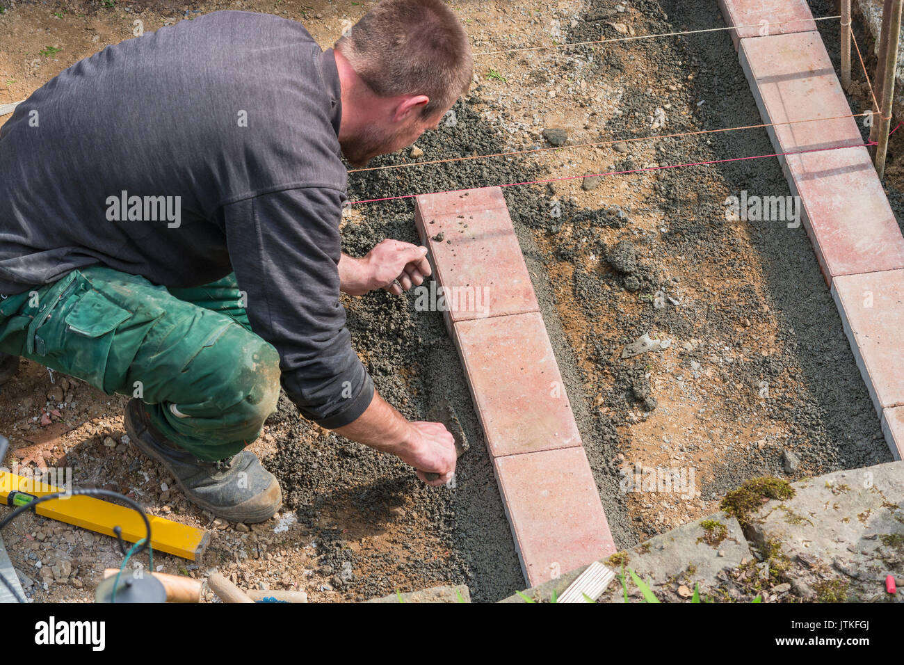 Workers in advance for laying paving stones and bricks. Various tools in the background. - Stock Image