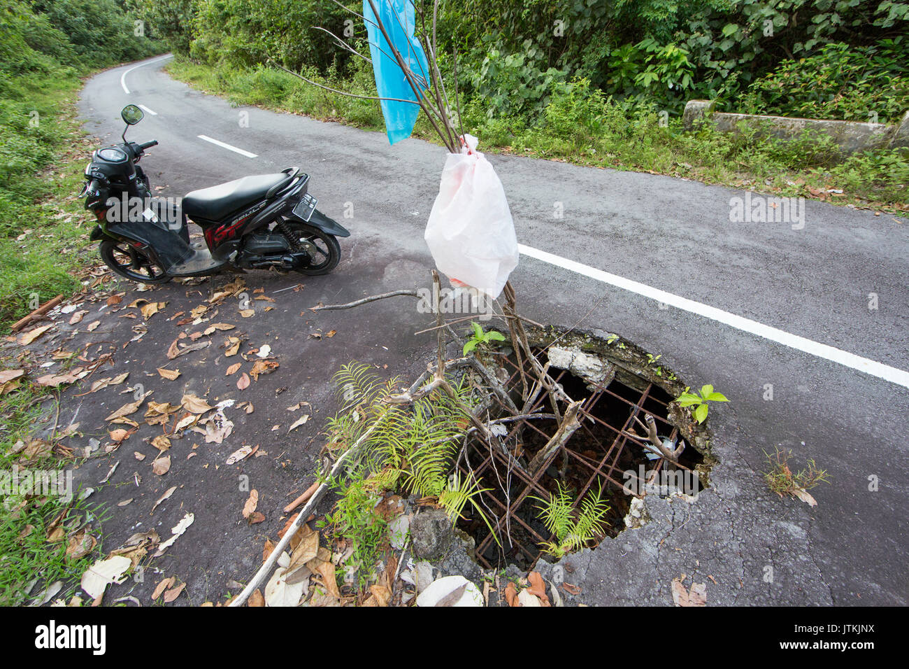 Huge pothole in road at Pulau Weh, Aceh, Indonesia - Stock Image