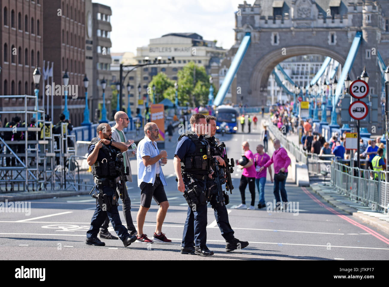 Armed police cross the road close to the start of the World Athletics Championships Marathon whilst final preparations are made. Tower Bridge, London - Stock Image