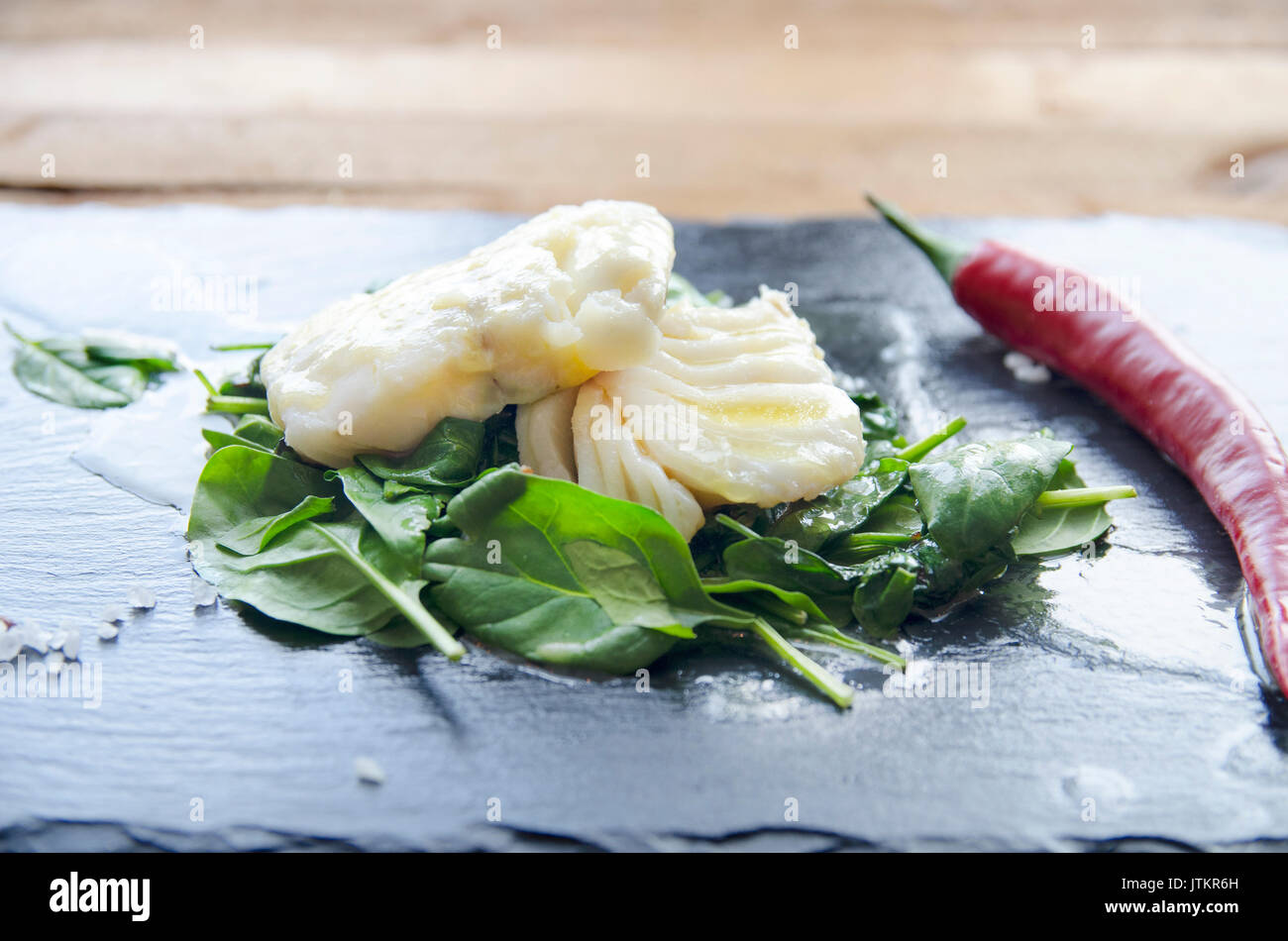 White fish fillet with herbs and chili on fried spinach. Gray background. - Stock Image