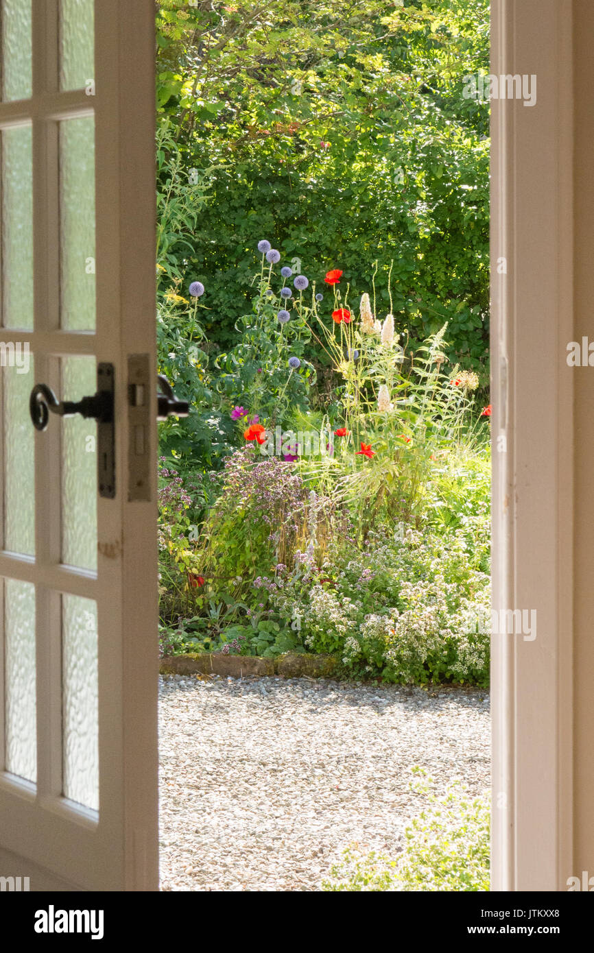 Front door opening out to colourful cottage style front garden in summer - Stock Image